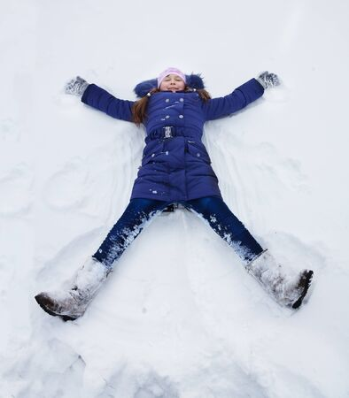 winter weather: Happy girl in blue bright clothes laying in star shape