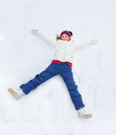 Happy girl in white bright clothes laying in star shape photo