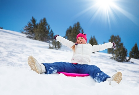 hands lifted: Happy girl sitting on sled with her hands lifted, wearing ski mask, in the mountains