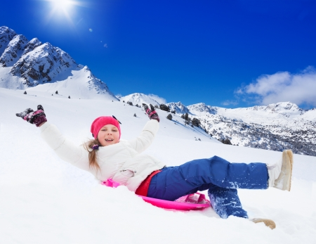 hands lifted: Happy girl sliding on sled with her hands lifted, wearing ski mask, in the mountains