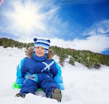 Happy, smiling boy sitting on sled, on slide in the forest photo