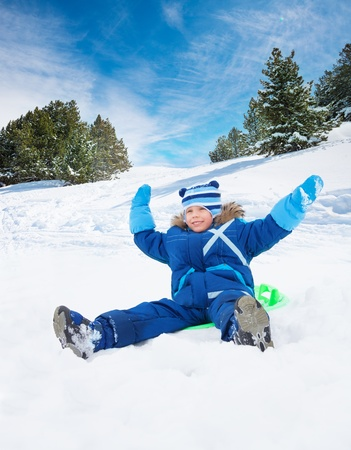Happy, smiling boy sitting on sled with her hands lifted, on slide in the forest photo