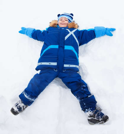 Happy boy in blue bright clothes laying in star shape photo