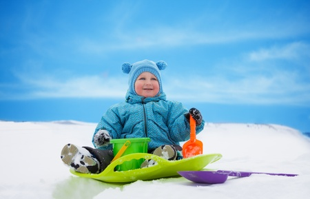 Happy toddler sitting on sled in snow in winter photo