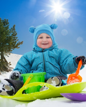 Close up of happy toddler sitting on sled in snow in winter photo