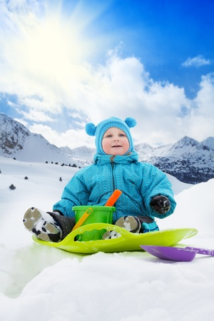 Close up of happy toddler sitting on sled in snow in winter in mountains and playing with scoop and bucket photo