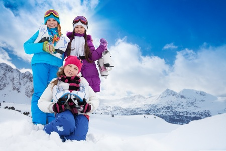 Three happy smiling Caucasian girls friends standing outside with ice-skates with mountain on background for copy space