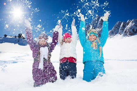 Three happy 10 years old girls throwing snow in the air at once photo