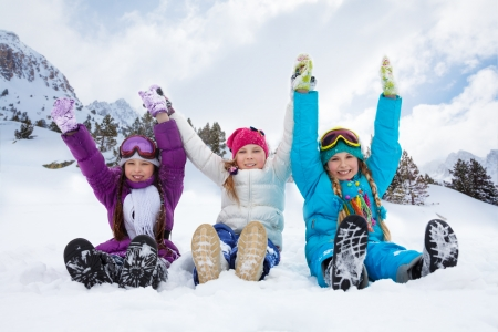 Group of three kids girls sitting in snow together holding hands photo