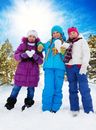 Three happy girls with heart shaped snowballs, standing together in the forest photo