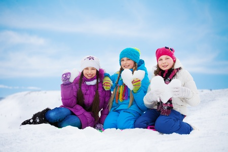 Three happy girls with heart made of snow, standing together outside in winter photo