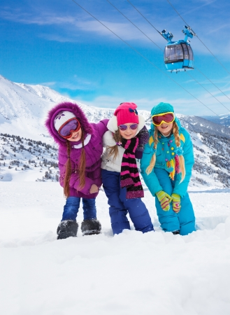 car lift: Three cute girls snowboarders in the mountain with ski lift on background