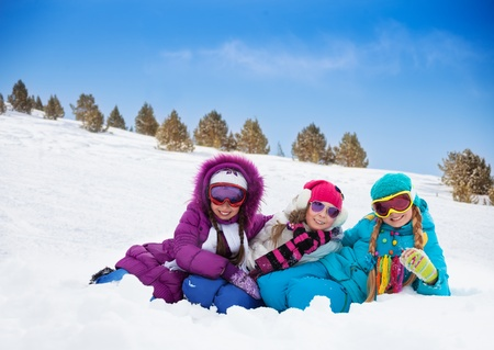 Three cute looking kids girls laying in snow together on sunny day photo