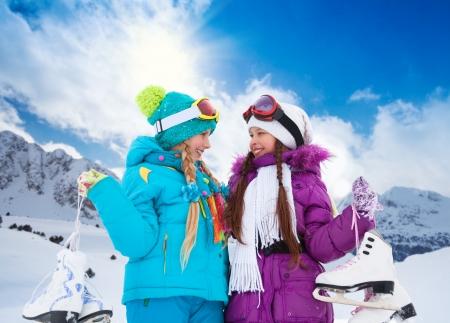 schaatsen: Close-up portret van twee gelukkige lachende blanke meisjes die buiten met schaatsen Stockfoto