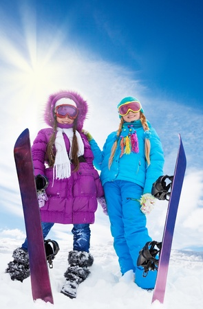 Two girls with snowboards together in snow having fun outside photo