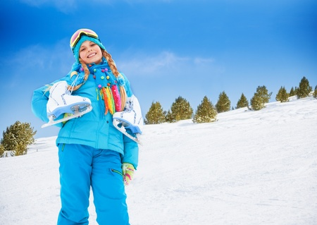 Smiling happy 10 years old Caucasian girl standing with ice-skates outside on winter day photo