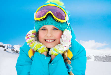 Mountain skier ten years old girl laying in snow with mountains on background photo