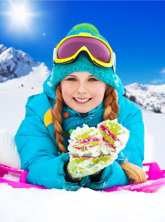 Happy 10 years old girl in color gloves lay in snow in mountains photo