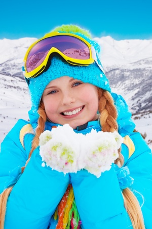 Happy 10 years old girl  showing pile of snow wearing beautiful fancy winter clothes and ski mask with mountains on background photo