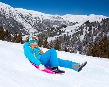 sledding: Happy girl sliding down the slope on sled, wearing ski mask, with mountains on background