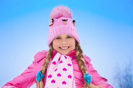 Close up portrait of cute smiling Caucasian girl in pink coat on sunny winter day photo