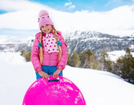 outwear: Happy girl in cute pink outwear and warm hat standing on the slide with sled in the mountains Stock Photo