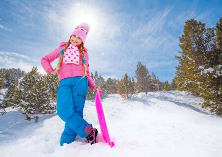 Smiling girl in cute pink outwear and warm hat standing on the slide with sled in the forest photo