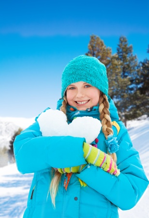 Beautiful happy girl hugging big heart made of snow standing outside in the forest photo