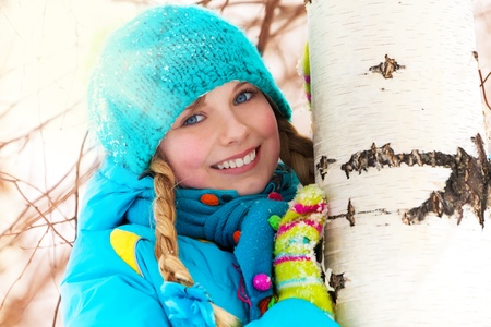 Portrait of little cute girl hiding behind the birch tree on winter snow day photo