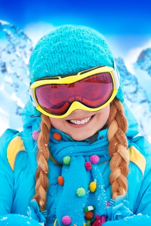 ski mask: Portrait of happy blond smiling girl with braids in winter clothing and ski mask