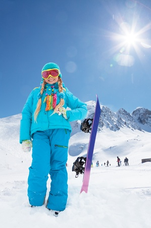 Cute blond 10 years girl with snowboard in the mountains photo