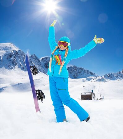 Portrait of blond 10 years old happy girl with snowboard in the mountains lifting hands from enjoyment photo