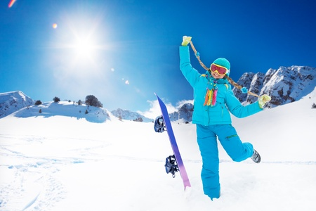 Portrait of cute blond 10 years girl jumping with skis in the mountains photo
