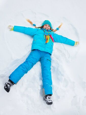 Happy girl in bright vivid blue clothes laying in star shape photo