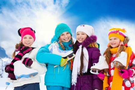 patinaje: Primer retrato de grupo de cuatro ni�as felices cauc�sicas amigos sonriendo de pie fuera de patines de hielo