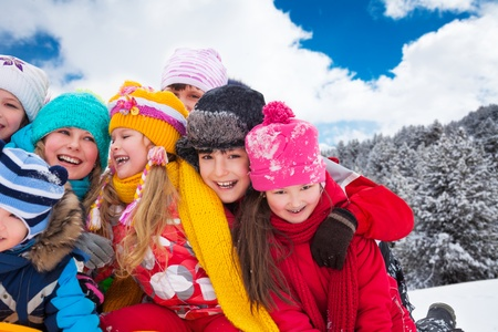 Group of diversity looking happy kids hugging and playing together on winter sunny day photo