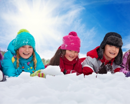 Group of three kids 5-10 years old boys and girls on snow in a row day in mountains photo