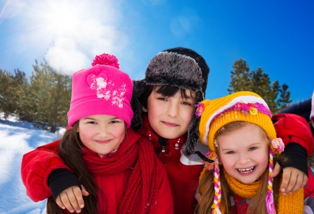 Three diversity looking kids - two girls and a boy outside on sunny winter day photo