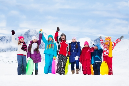 winter day: Row of large group of kids, friends, boys and girls standing together outside in snow and waiving hands