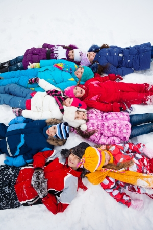 Large group of kids 5-10 laying in snow together, view from above photo