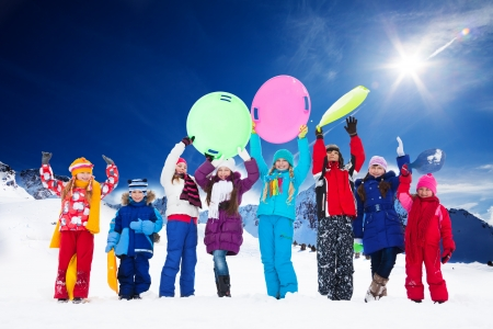 Row of large group of kids, friends, boys and girls standing together outside in snow, waiving hands, many holding sled Stock Photo