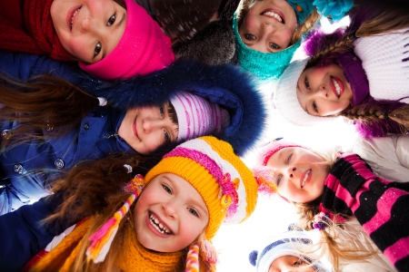 people laughing: Group of happy kids look down wearing winter clothes Stock Photo