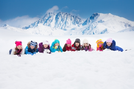 Large group of diversity looking kids 5-10 years old boys and girls on snow in a row day in mountains