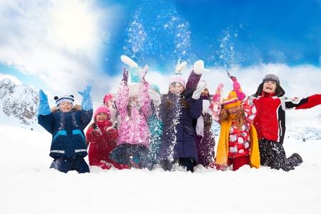 Grote groep van diversiteit kijken kinderen jongens en meisjes werpen sneeuw in de lucht samen Stockfoto