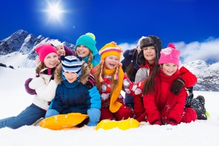 Group of kids together hugging and laughing sitting in the snow on sunny day photo