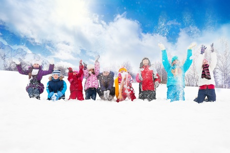 Large group of diversity looking kids boys and girls throwing snow in the air together sitting in a row
