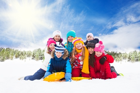 Group of kids together hugging and laughing playing on sunny day photo