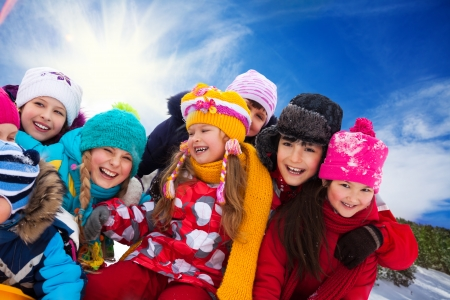 Group of diversity looking happy kids together on winter sunny day