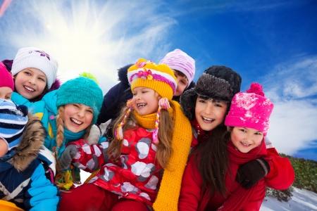 fille hiver: Groupe de la diversit� � la recherche des enfants heureux ensemble sur l'hiver journ�e ensoleill�e