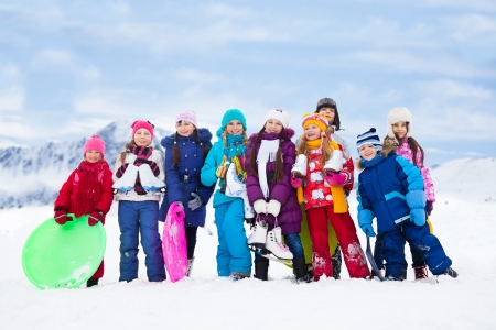 Group of kids together outside in snow with sled, ice skates having fun with winter activities photo